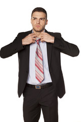 attractive businessman unfasten the tie on white background