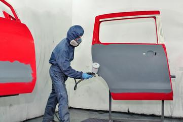 Worker painting car door.