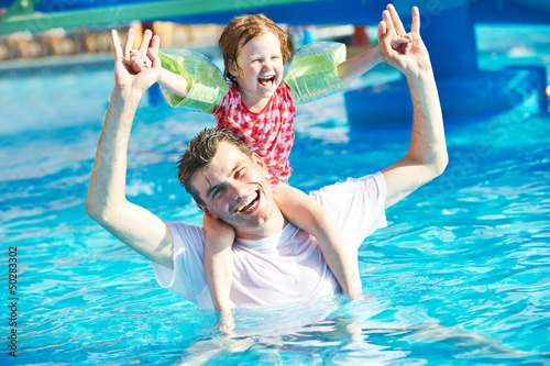 Father and child in resort swimming pool