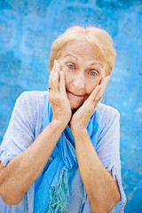 Portrait of surprised senior woman with hands on face on blue ba