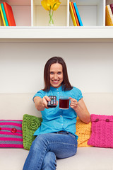 woman holding cup of tea and remote controller