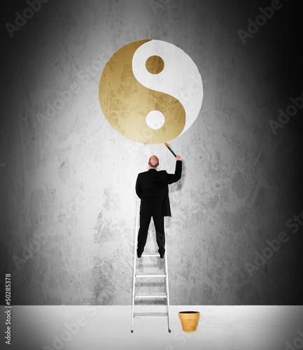 Work life balance concept - man painting golden yin-yang symbol
