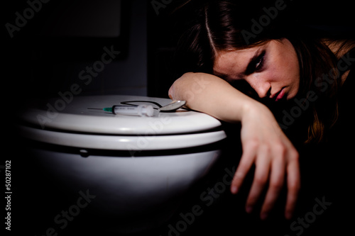 Heroin addict leaning on the toilet after getting high