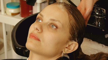 Beautiful young woman getting a hair washed at a hair salon.