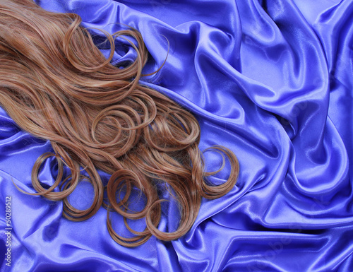 curly brown hair on blue silk textile