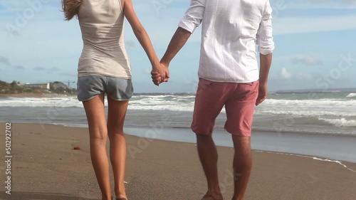 Happy young pair walking on a coastline