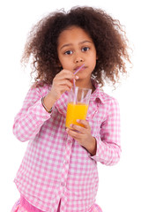 Little african asian girl drinking orange juice