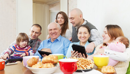 happy multigeneration family uses electronic devices
