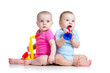 Funny babies girl and boy  playing musical toys. Isolated on whi
