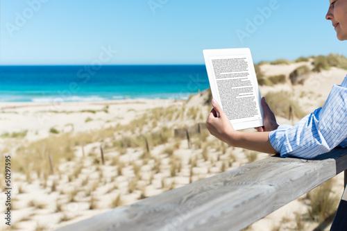 frau liest ein ebook am strand