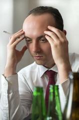Depressiver Geschäftsmann raucht und trinkt