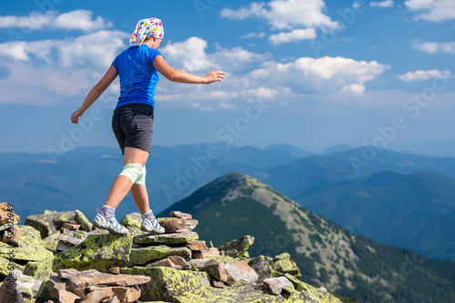 Athlet looking girl with bandage on knees jumps over stones in C