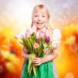 kleines Mädchen im Dirndl und mit Blumenstrauss