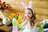 Happy easter bunny girl with easter eggs sitting in country hous