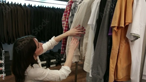 Young woman looking at clothing on rack