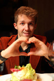 Happy young man with his hands depicting heart