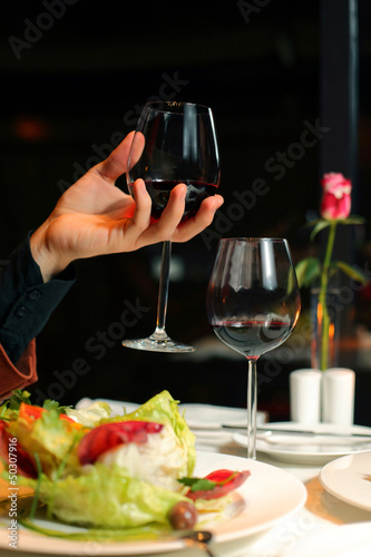 hand holds a glass of wine on a dark background