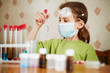 Girl in t-shirt in respirator attentively looks at test tube