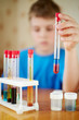 Boy in blue t-shirt sits at table with chemical reagents