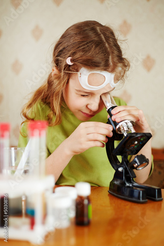 Girl in green t-shirt attentively looks into microscope