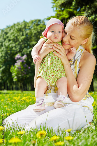 Young smiling mother sits on grass in park and holds her baby