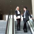 Business couple talking on escalator.