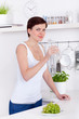 young woman drinking a bottle of water in her kitchen