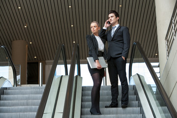 Young business couple on escalator.