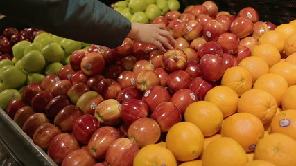 Women Selecting Organic Red Apples to Buy