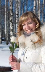 Pretty young woman with rose , winter season