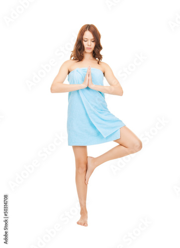 beautiful woman meditating in towel