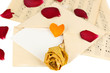 Old envelope with blank paper and dried rose