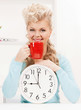 attractive businesswoman with clock and red cup