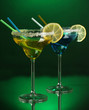 Yellow and blue cocktails in glasses on color background