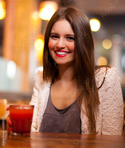 Young woman drinking in a bar
