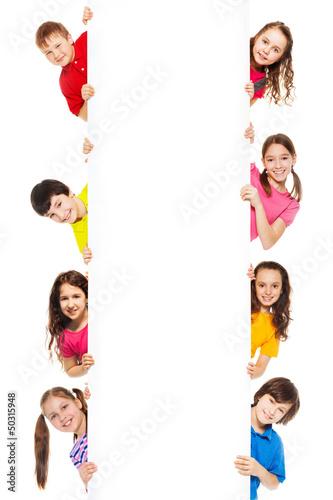 Six kids looking from blank billboard