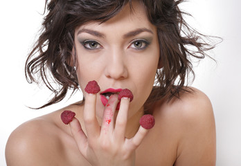 Sexy diet. Beautiful woman eating raspberries from fingers
