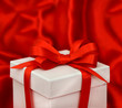 white gift box with red bow ribbon