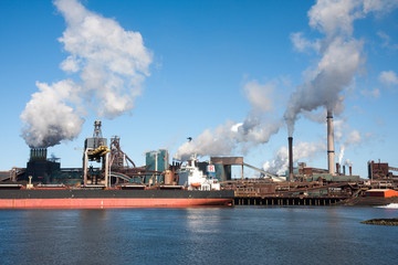 Big ship in front of a large steel factory in IJmuiden, Netherla