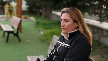sad women sitting a bank, steady cam shoot