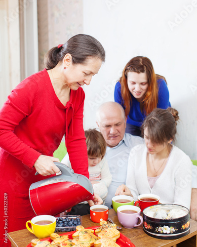 woman in red pours tea for family