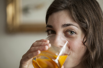 Young Woman with Beautiful Green Eyes Drinking Mango Juice