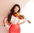 Pretty young female playing the violin, soft focus.