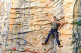 man on rock wall in sport center