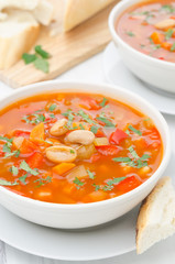 Vegetable soup with white beans in a bowl closeup vertical
