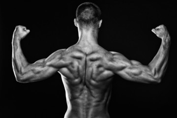 Muscular male persons back on black background