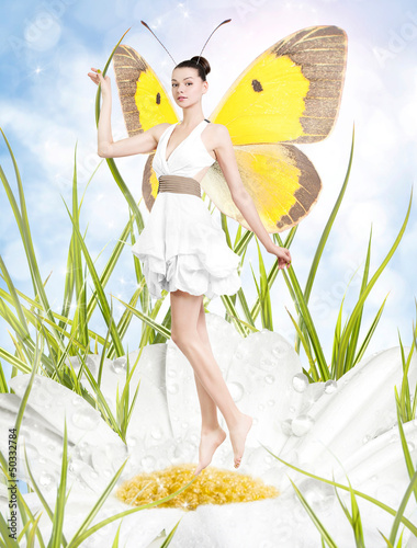 Beautiful young woman as butterfly on spring daisy