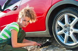 A beautiful young woman reparing a car