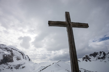 cross on top of swiss mountain in winter