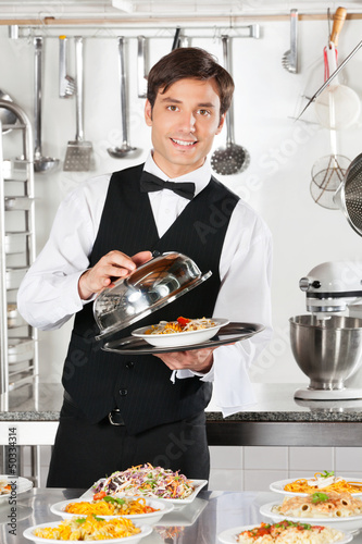 Waiter Lifting The Cover Of Cloche
